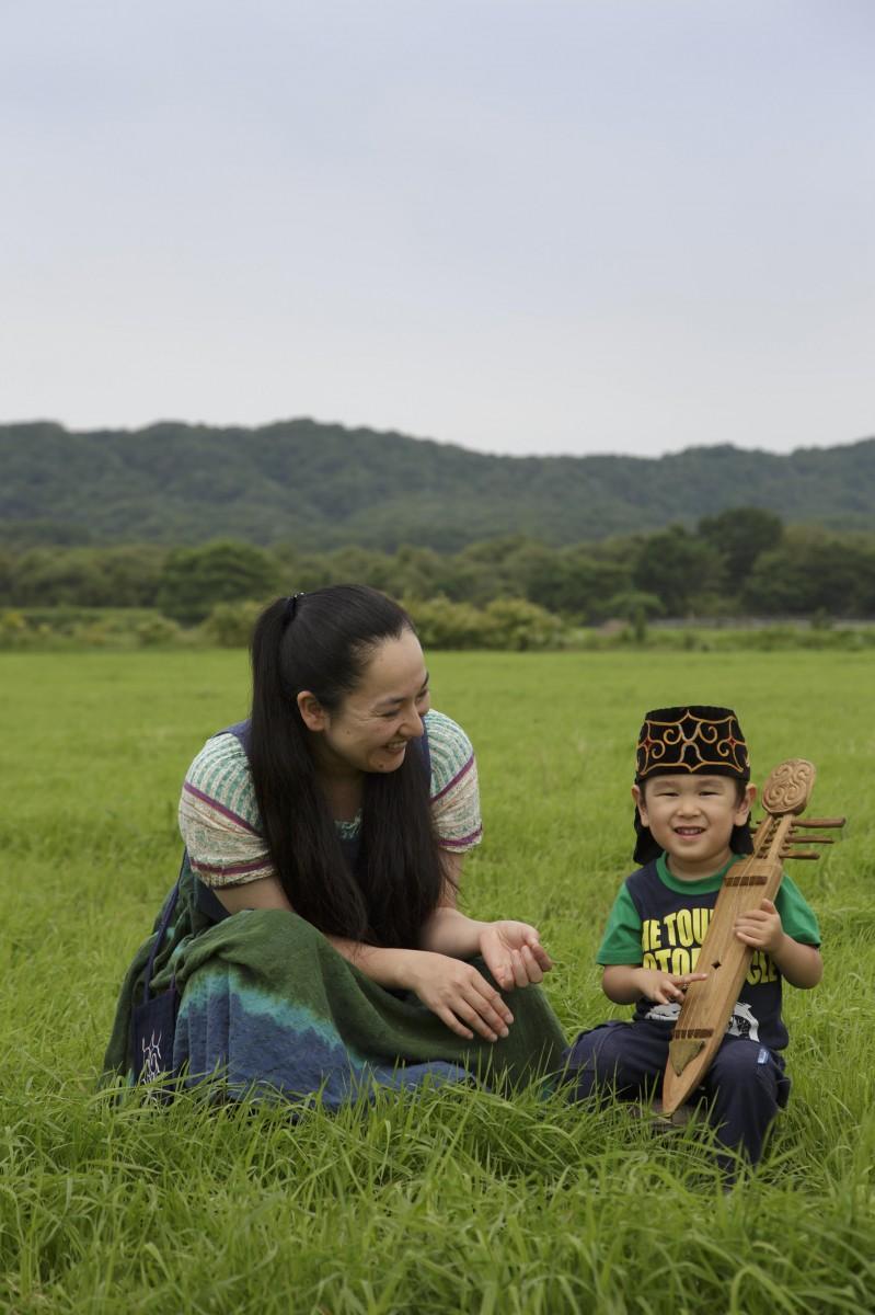 大草原に座るアイヌ民族