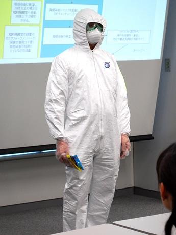 研修中にゴーグル、マスク、ゴム手袋と防護服を身にまとった社員が登場