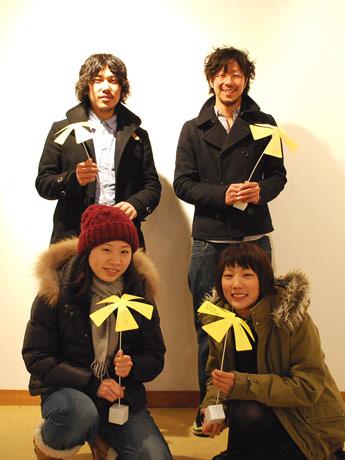 「シンサイミライノハナ」を手に微笑む、西川さん、萩原さんら実行委員会メンバー