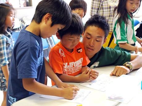 3本に折った短い鉛筆で名前を書く子どもたち