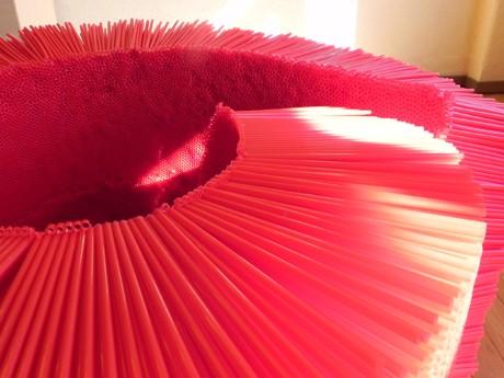 赤いストローを束ねて作られた大きな作品が展示されモダンな空間を創り上げている