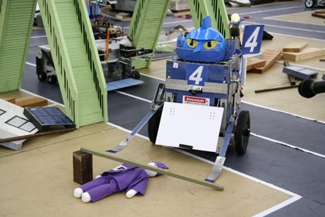 人形にかぶさるがれきを除去するレスキューロボット(写真提供=レスキューロボットコンテスト実行委員会)
