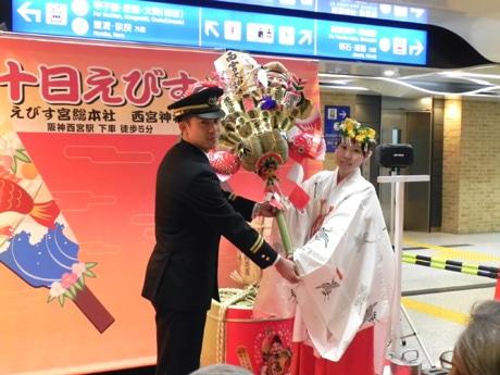 西宮神社の巫女(みこ)から三宮駅の上島慎平駅長に特製大熊手が贈られた