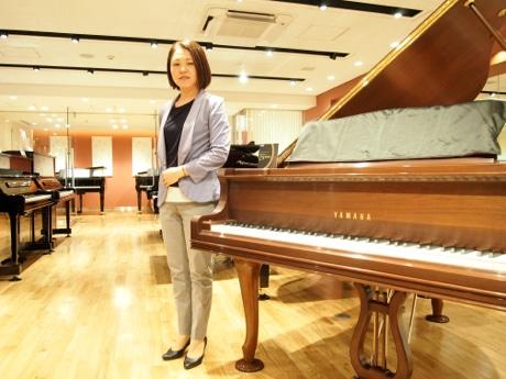 店長の嶋根さんとピアノの試奏室(写真奥)ピアノの展示台数も増やした