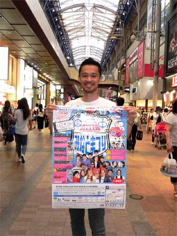 「第15回 Kobe Love Port・みなとまつり」ポスターを持つみなとまつり委員会広報担当の櫻井高幸さん