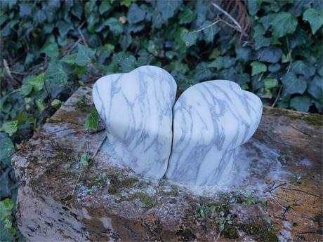 「うろこの家」の庭で磨くハートの形の石