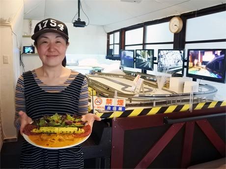 野菜を山、カレーを海に見立て、トンネルに挟まれた新神戸駅に止まっているドクターイエローを表現した1周年特別メニュー「新神戸」を持つ店長兼シェフの佐々木麻美さん