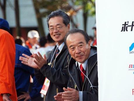 2011年11月20日に開催された「第1回神戸マラソン」ゴールでランナーを出迎える前会長の植月正章顧問(右)