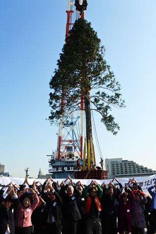 「世界一のクリスマスツリー」の前で「あすなろポーズ」を取るプラントハンター西畠清順さんら