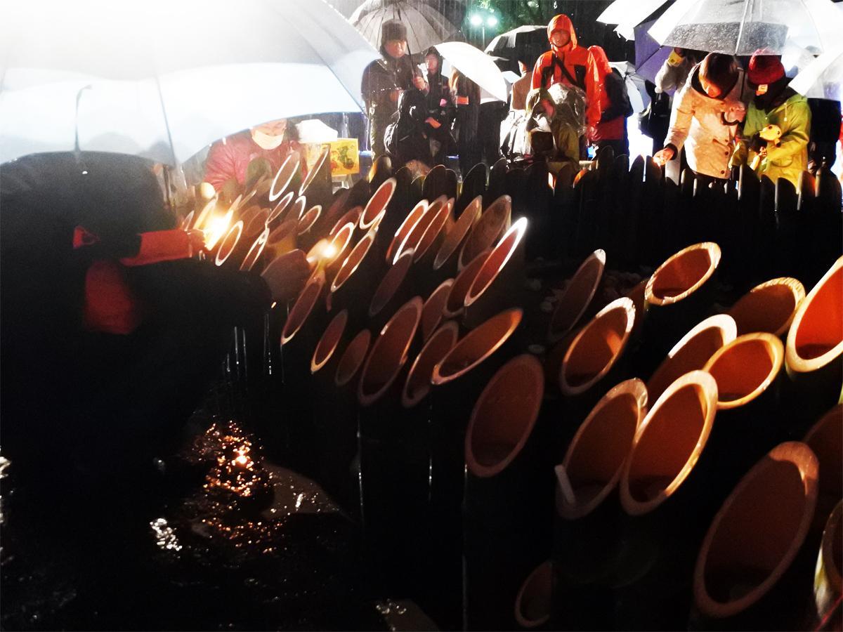 あいにくの雨の中、参加者が竹灯籠の中のろうそくに点灯