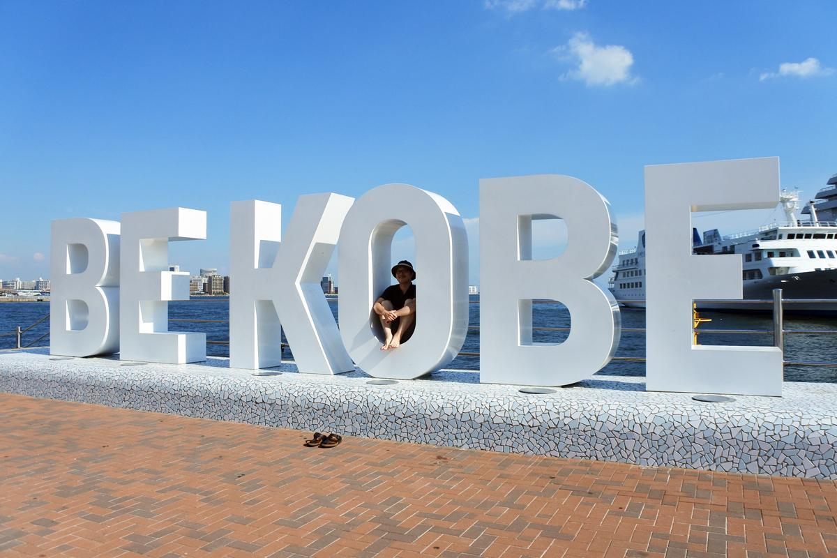 靴を脱いで「BE KOBE」のモニュメントで記念撮影する大橋一馬編集長
