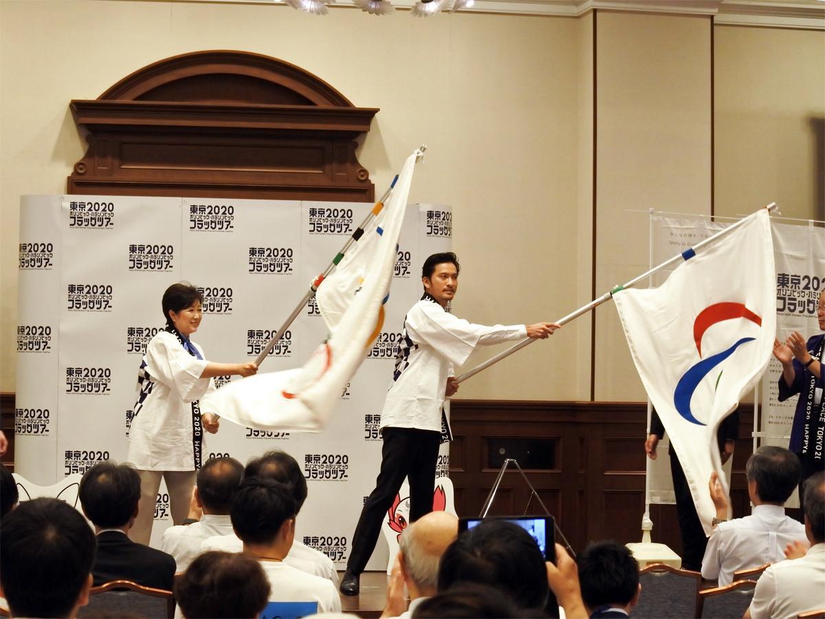フラッグを振る小池百合子東京都知事とスペシャルアンバサダーの長瀬智也さん