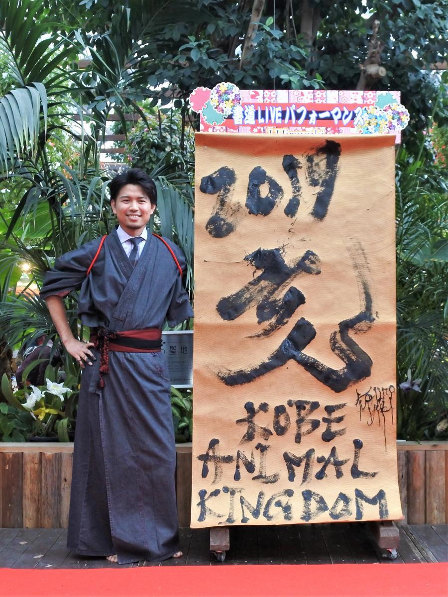 金色の紙に書いた「亥」の文字と記念撮影する書家・J.Hiroyuki(慈英裕之)さん
