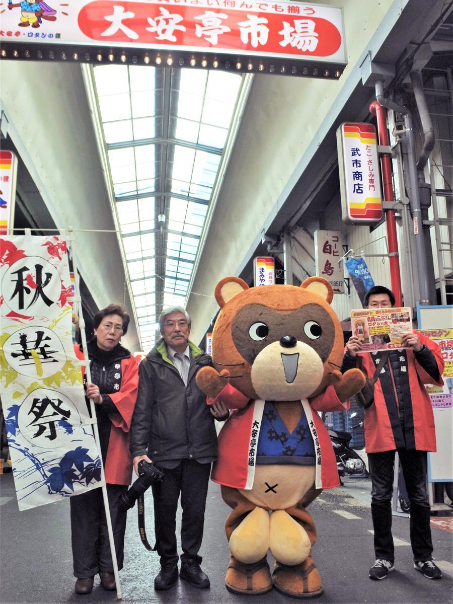 大安亭市場協同組合の桑山鉄男理事長(左から2番目)とマスコットキャラクターの大安亭ロダン
