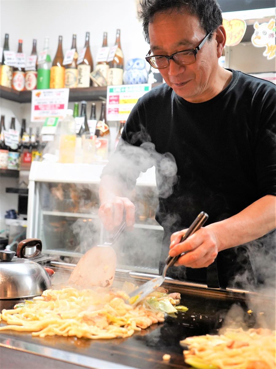 鉄板カウンターに立つ「佐用名物 ホルモン焼きうどん こうちゃん」店主の西坂明弘さん