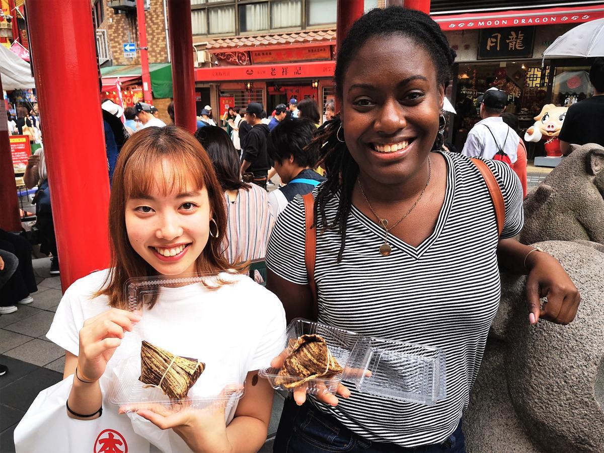 ちまきの食べ比べを楽しむ米ペンシルベニア州出身のシャネ・ブラウンさんと神戸南京町「ゲストハウス神戸なでしこ屋」スタッフ