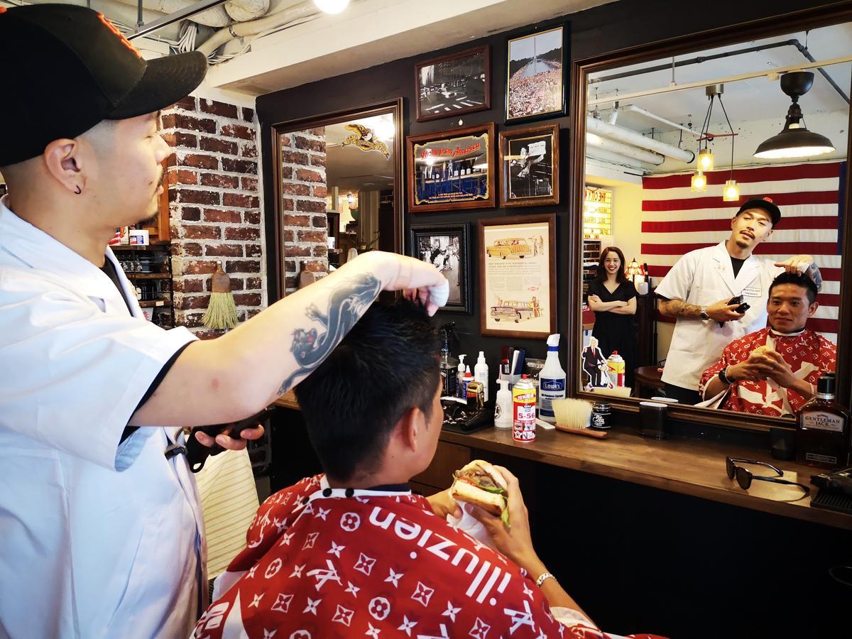 ハンバーガーを食べる常連客をヘアカットする店主の小野原祐輔さん