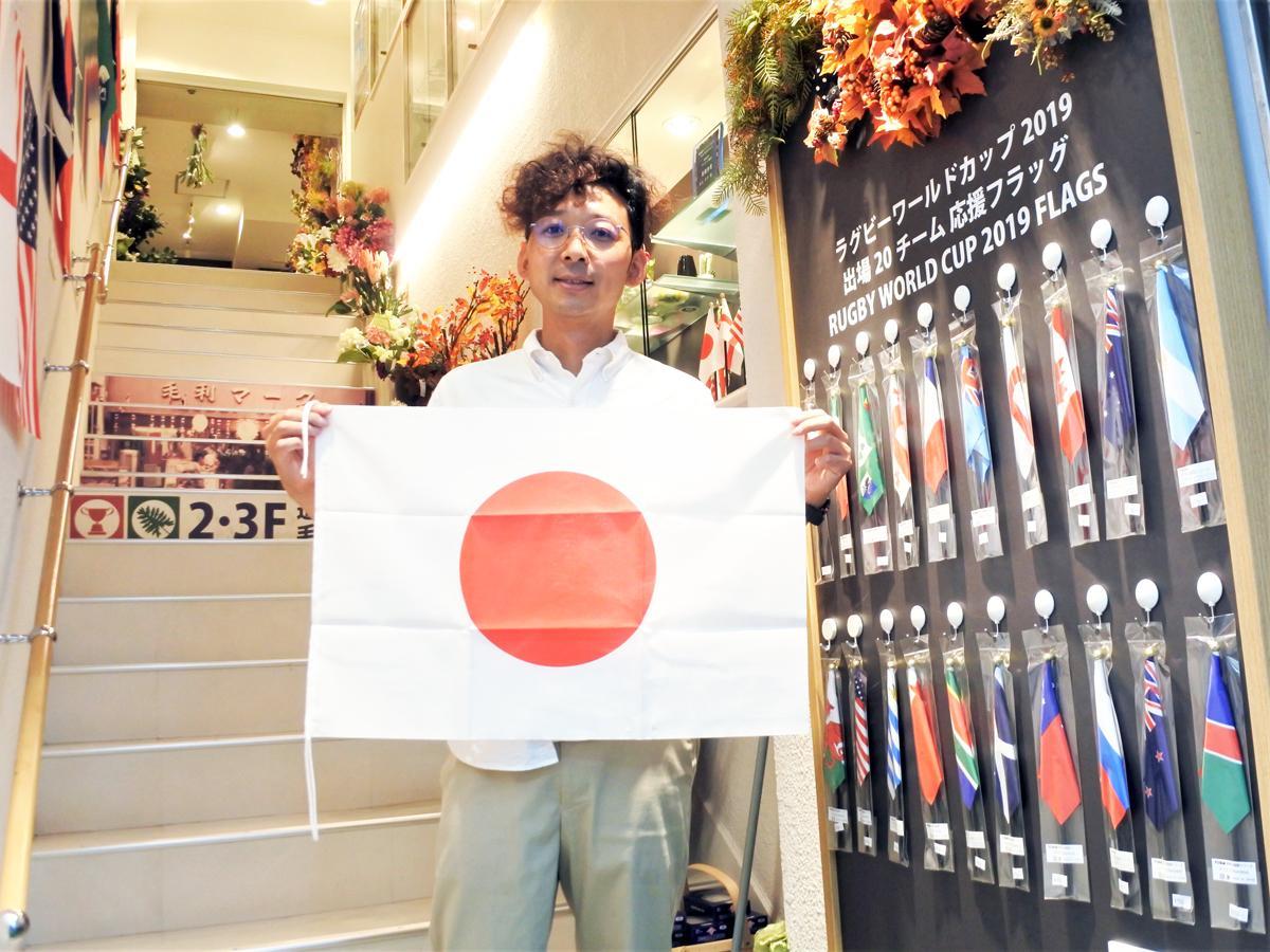 「応援フラッグ」を持つ老舗雑貨店「毛利マーク」5代目社長の藤井淳史さん