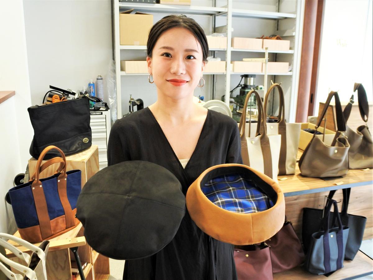 職人とのコラボ新商品「レザーベレー帽」を持つ店長の坂本瑞己さん