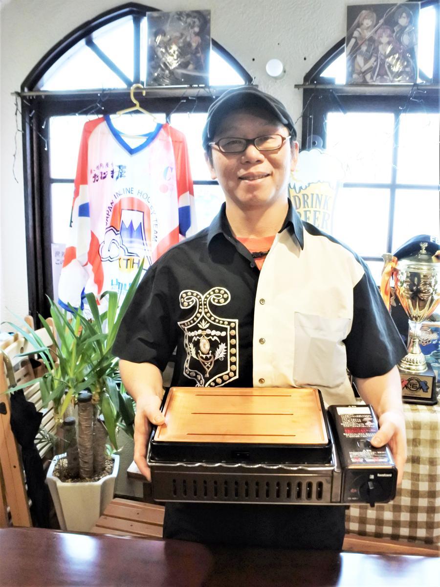 焼き肉用のオリジナル銅板を持つ店主の岩村隆史さん