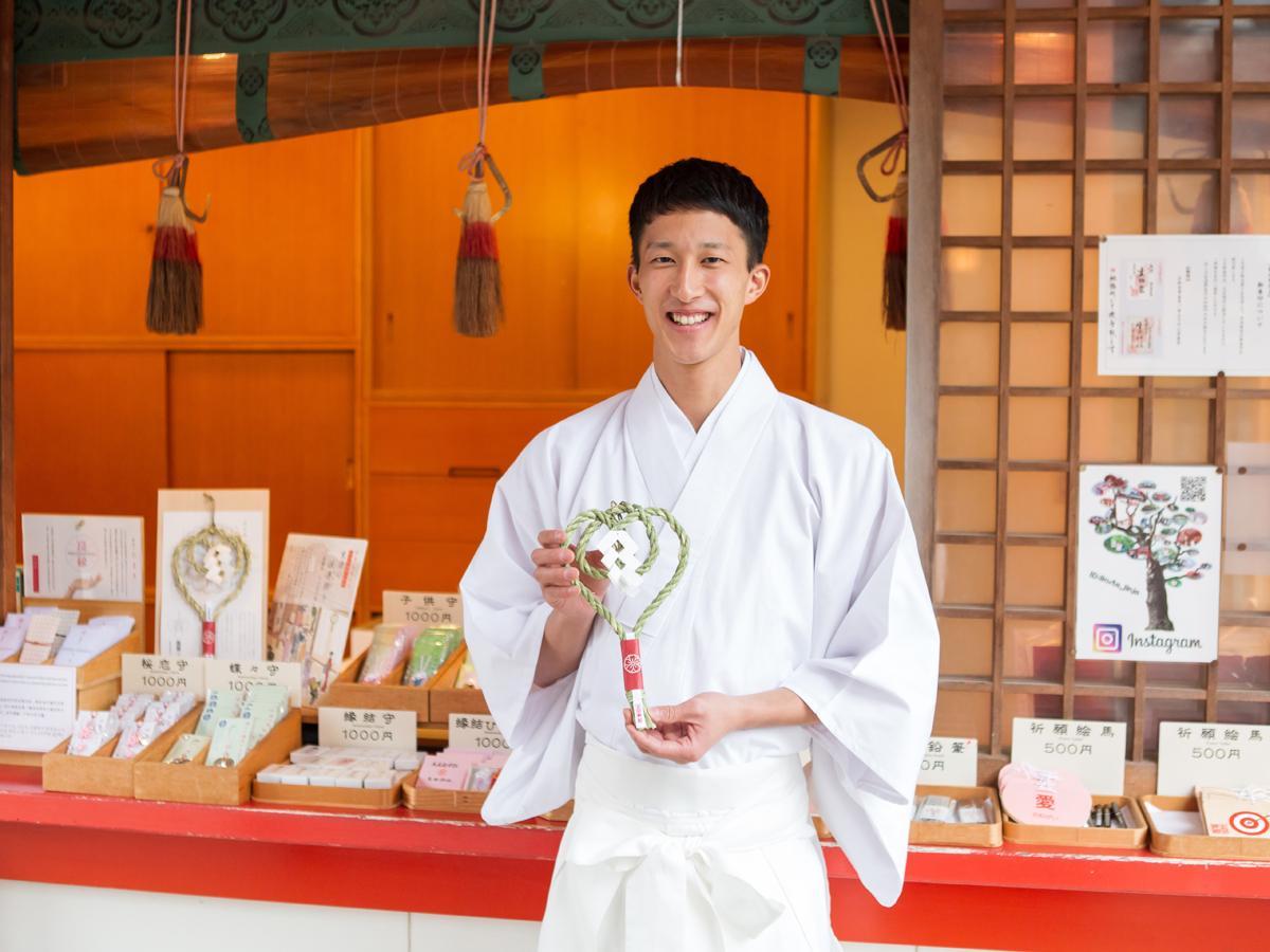 正月用の生田神社オリジナルしめ飾りを持つ出仕の宮脇正行さん 撮影=金本義隆さん