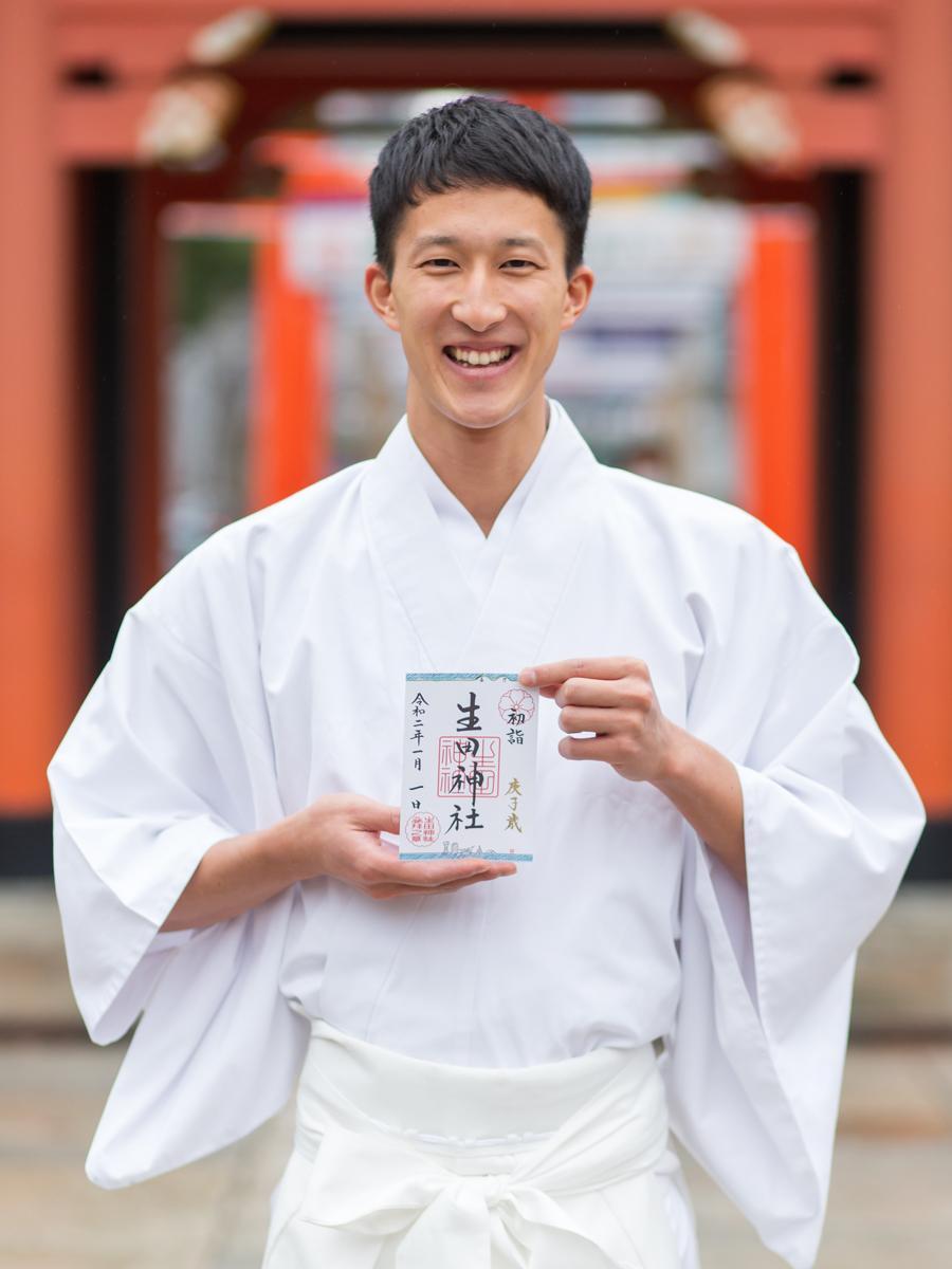 神戸の港と六甲山をモチーフにした1月限定御朱印を持つ出仕の宮脇正行さん 撮影=金本義隆さん
