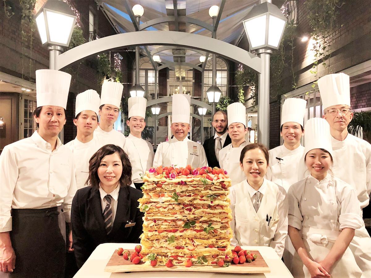 巨大なイチゴの「ミル・ミルフィーユ」を囲む総支配人・総料理長の山口浩さん(中央)とスタッフら