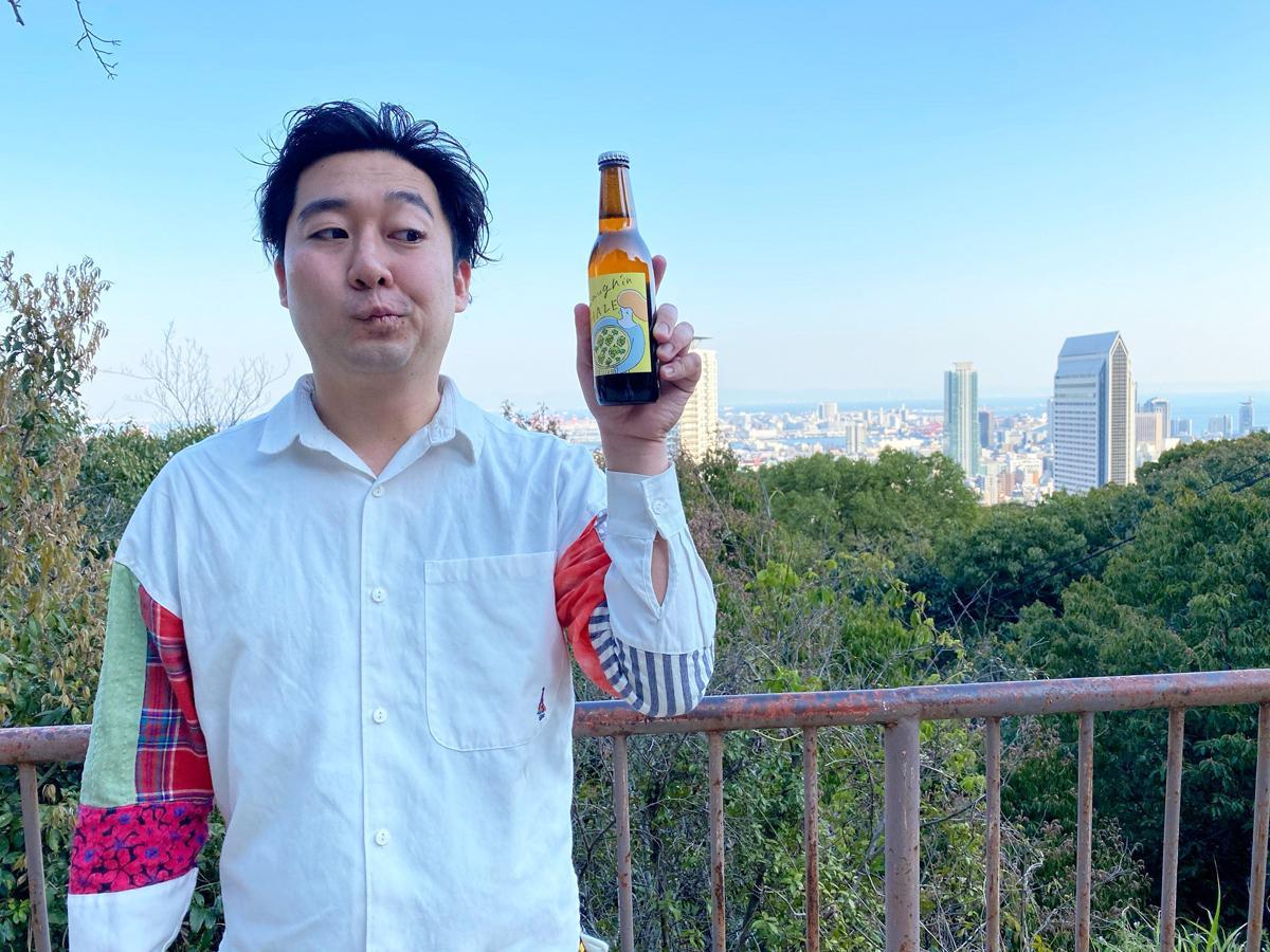 三宮のビアバー「Beer Cafe Laugh'in(ビア カフェ ラフィン)」のオリジナルクラフトビール第2弾「Laugh'in HAZE(ラフィンヘイズ)」を持つ店主の秋田壮馬さん