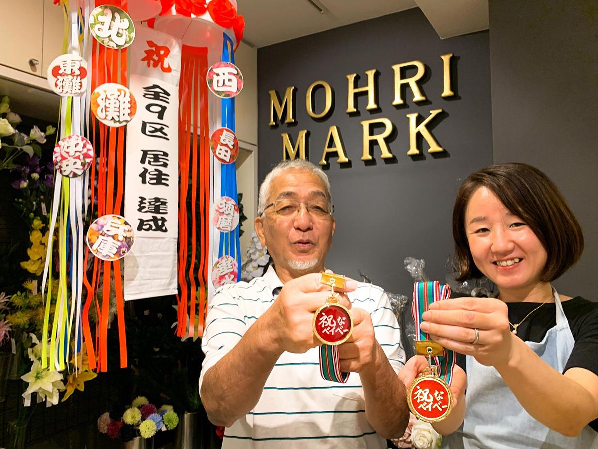 「祝なメダル」を発売した老舗雑貨店「毛利マーク」の毛利二三夫さんと藤井美香さん