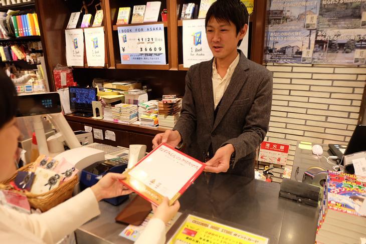 絵本購入者から「ブックサンタ」活動申し込みを受ける書店スタッフ