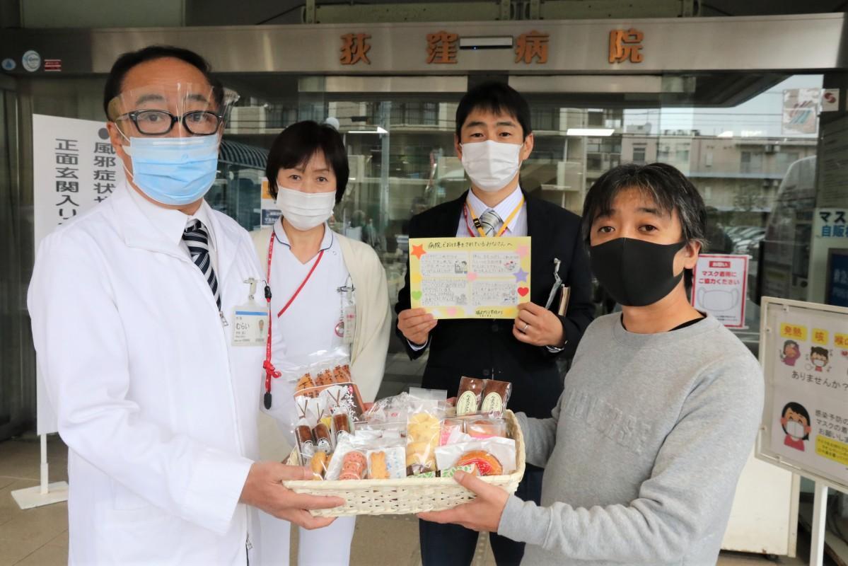 障害者施設職員から、菓子詰め合わせを受け取る村井院長ら