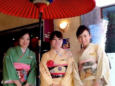 女性フロントスタッフが着物姿で宿泊客を出迎える
