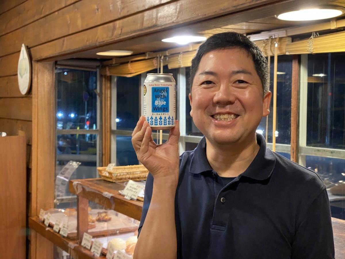 サンプル缶を手に持つプロジェクトリーダーの奥山誠さん