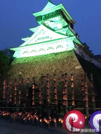 竹灯籠や番傘などのイルミネーションとともに、緑色のライトアップに彩られた小倉城