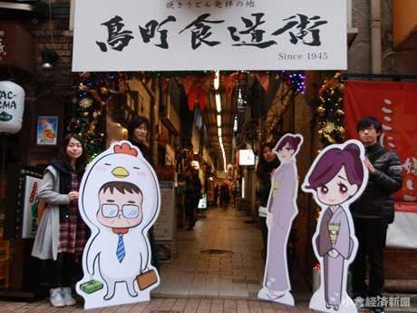 「鳥町食道街」入り口でキャラクターを披露する「西日本工業大学」デザイン学部の学生ら。左端=城野絵美さん。