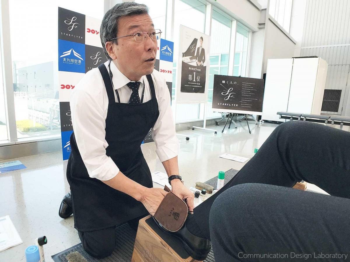 搭乗客の靴を磨く「スターフライヤー」社長の松石禎己さん