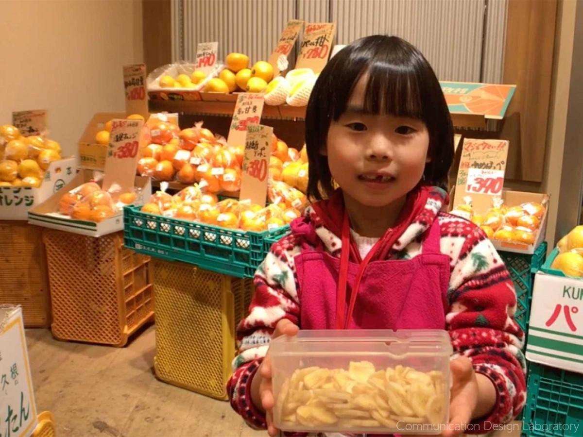 やおや「植木商店」店頭で来店客にバナナチップを勧める小学生