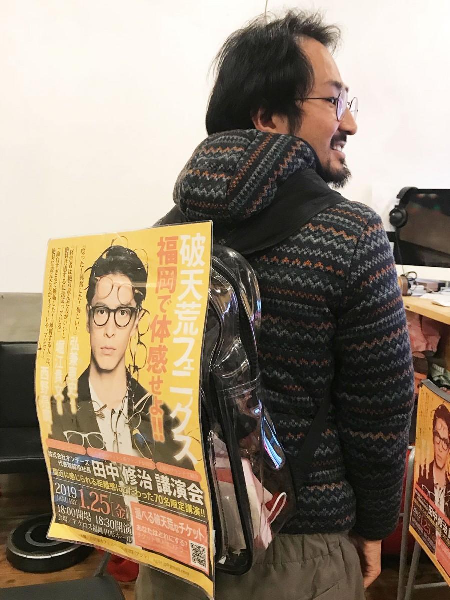「移動中にも生産性を」と、自作のポスターを背中に本を売り歩く時松さん