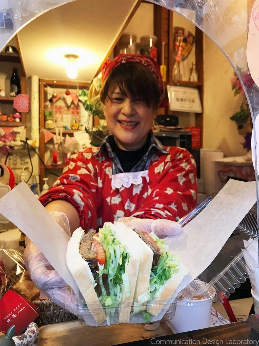 テークアウト用の小窓から笑顔でサンドイッチを提供する「純蓬」さん