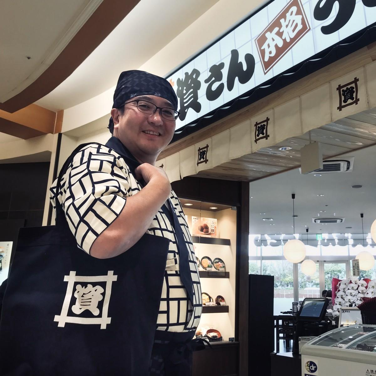 オリジナルトートバッグを肩掛ける佐藤崇史社長