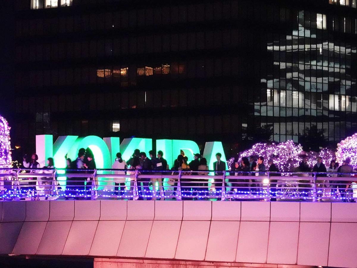 「鴎外橋」上のKOKURAサインモニュメントと、市役所壁面に映り込む小倉城