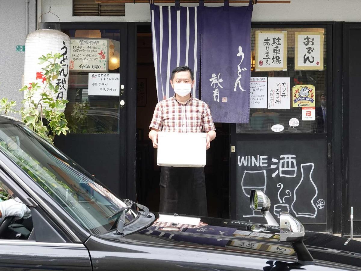 「うどん秋月」で配送用の商品を持つ時津雄大さん
