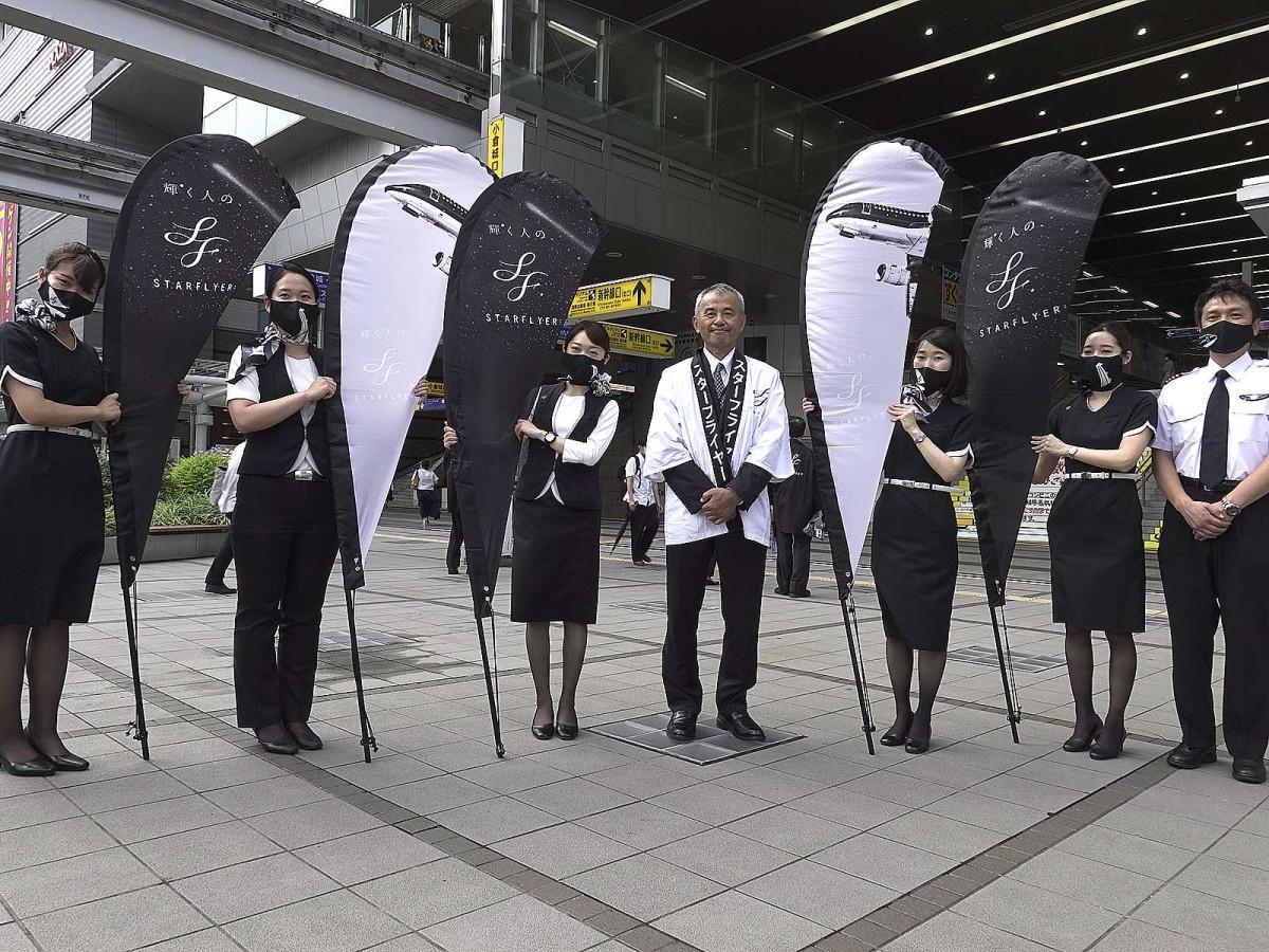チラシを配布した新社長の白水政治さん(写真中央)
