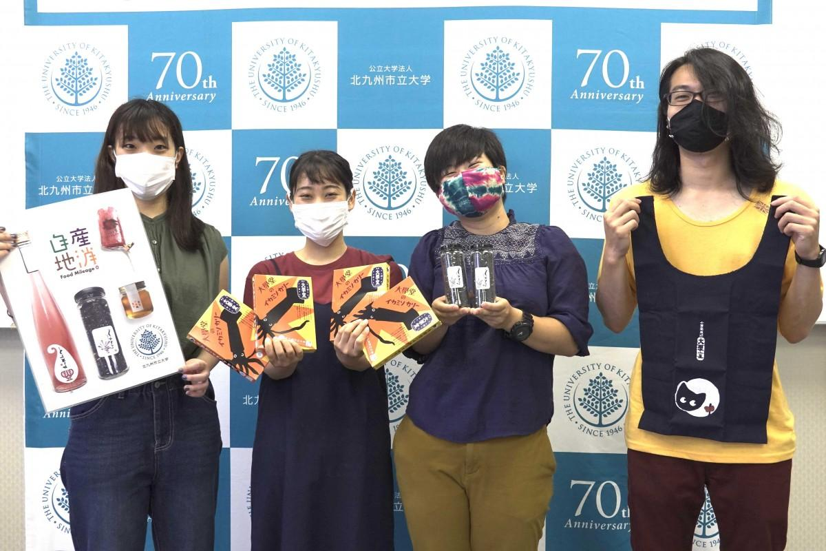 「自産地消」をテーマに活動する「九州フィールドワーク研究会」メンバー。(左から)今里咲輝さん、緒方良子さん、兵頭エマさん、田中幹哉さん。古代米やエコバッグも販売する。