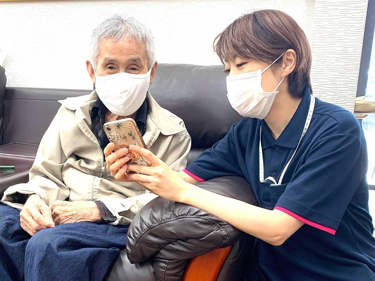 椛山さんの事業所「ホームタウン大里」でアプリの説明をする介護スタッフ
