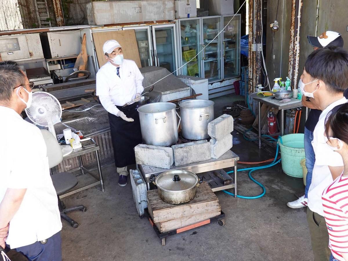 店舗前に設置したずんどう釜を見せ、豚骨スープの抽出方法を説明する秋武政道さん