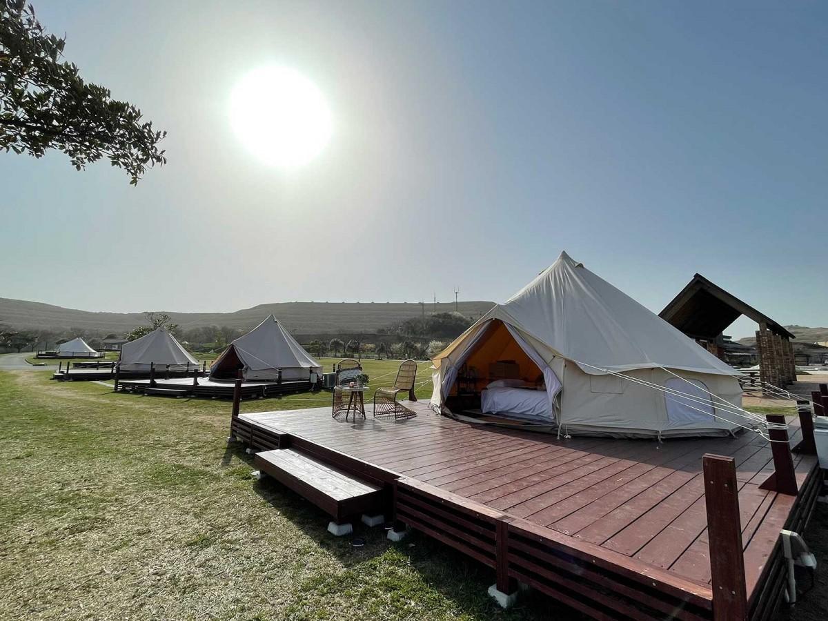 360度のカルスト台地を臨む芝生広場に設置したグランピングテント