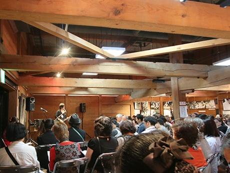 木のぬくもりを感じる片倉シルク記念館、100人を超える観客が集まった。