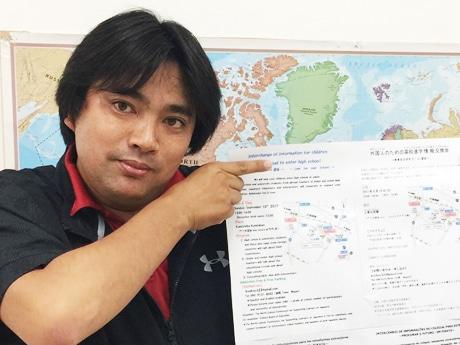 5ヶ国語で印刷されたチラシを手にする当間さん。地域の多文化交流を活性化するグループ「光KISHIN」の代表でもある。