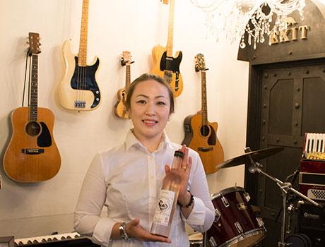 オリジナル日本酒を手にするAmiさん。店内の楽器は自由に触れることができる。